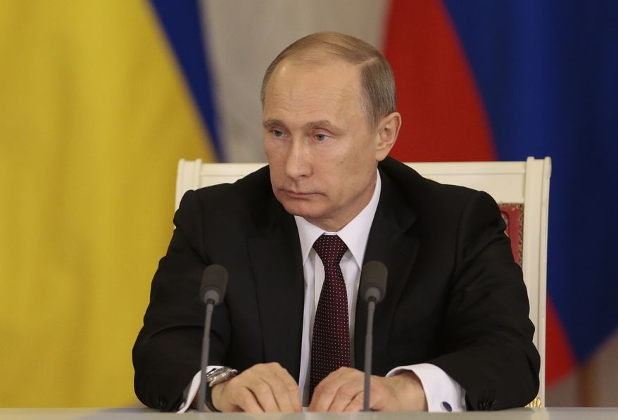 Russian President Vladimir Putin reacts during a news conference after meeting with his Ukrainian counterpart Viktor Yanukovych in Moscow on Tuesday, Dec. 17, 2013.  Russian President Vladimir Putin says Moscow has agreed to sharply cut the price for its natural gas supplies to Ukraine and will buy $15 billion worth of Ukrainian government bonds, but says there was no discussion about Ukraine joining a free trade pact of three ex-Soviet nations. (AP Photo/Ivan Sekretarev)