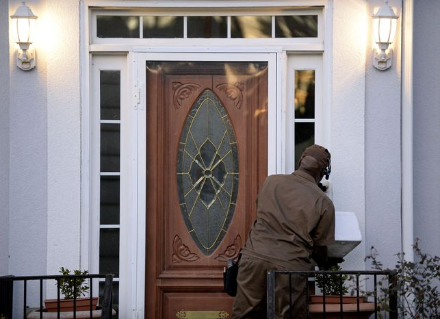A UPS driver rings the doorbell at the home listed for one of two Mega Millions lottery ticket winners that were identified by lottery officials in the $636 million drawing, Wednesday, Dec. 18, 2013, in Stone Mountain, Ga. (AP Photo/David Tulis)  ** FILE **