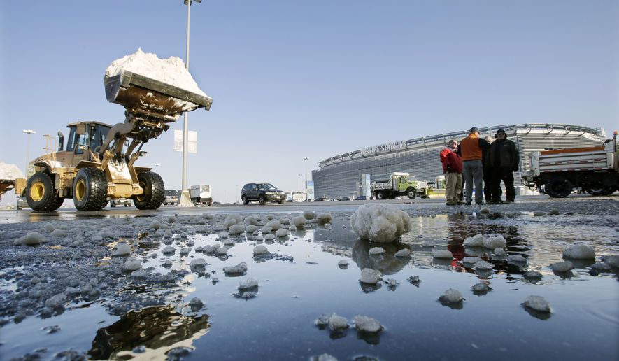 Workers remove snow from parking lots at MetLife stadium in East Rutherford, N.J., Wednesday, Dec. 18, 2013. Later officials demonstrated snow removal and melting machinery and outlined emergency weather scenarios and contingency plans for the Super Bowl in February. (AP Photo/Mel Evans)