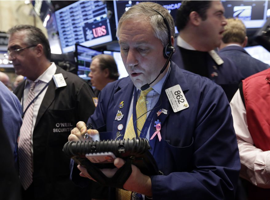 Trader Warren Meyers, center, works on the floor of the New York Stock Exchange, Wednesday, Dec. 18, 2013.  Stocks were modestly higher in early trading on Wall Street Wednesday as the Federal Reserve ends its last two-day policy meeting of 2013. (AP Photo/Richard Drew)