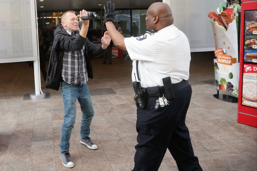 A security guard tries to prevent video journalist Bill Gorman from covering a protest at a McDonald's restaurant inside the Smithsonian's National Air and Space Museum this month. Little time is spent training guards to respond to unusual situations, a Government Accountability Office report says. (Associated Press)