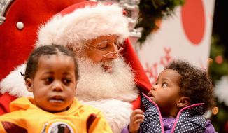 Christmas Color: Gyasi and Zara Cash of Temple Hills, Md., visit a popular black Santa Claus at the Mall at Prince George's in Hyattsville. (Andrew Harnik/The Washington Times)