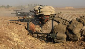 ** FILE ** U.S. Marines fire at Taliban positions, during a firefight in Nawa district, Helmand province, southern Afghanistan, Friday, Oct. 2, 2009. (Associated Press)