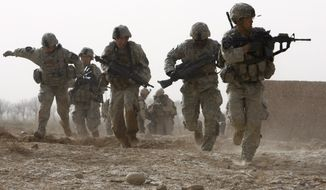 A U.S. soldier returns fire as others run for cover during a firefight with insurgents in the Badula Qulp area, west of Lashkar Gah  in Helmand province, southern Afghanistan, Sunday, Feb. 14, 2010. The unit is operating in support of a U.S. Marine offensive against the Taliban in Marjah area. (AP Photo/Pier Paolo Cito)