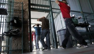 ** FILE ** Illegal immigrants prepare to enter a bus after being processed at Tucson Sector U.S. Border Patrol Headquarters Thursday, Aug. 9, 2012, in Tucson, Ariz. New strategies being implemented by the U.S. government, including the halting of one-way flights back to the interior cities in Mexico, are in place to streamline processing and expedite a return to Mexico. (AP Photo/Ross D. Franklin)