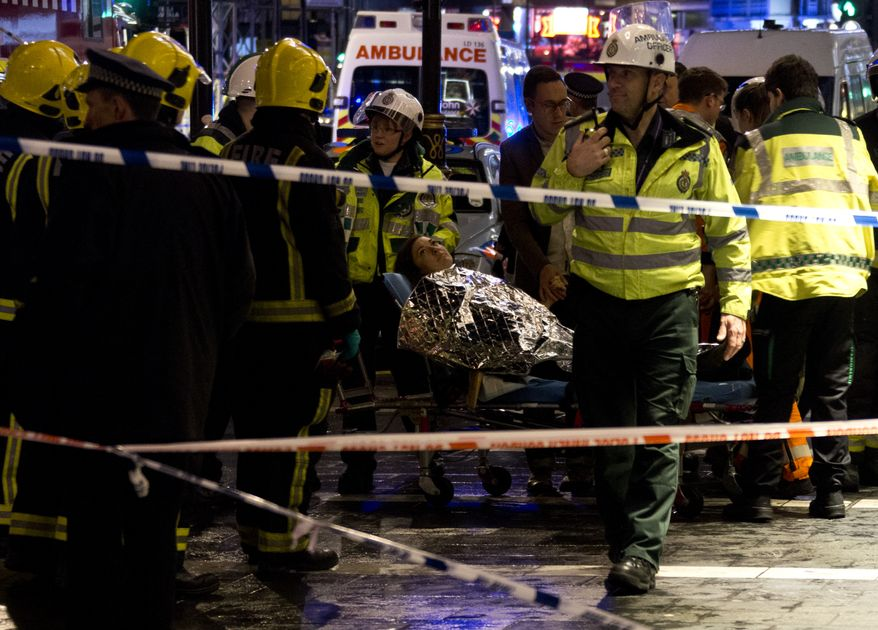 """A woman lies on a stretcher surrounded  by rescue workers, awaiting evacuation  following an incident during a performance at the Apollo Theatre, in London's Shaftesbury Avenue, Thursday evening, Dec. 19, 2013, with police saying there were """"a number"""" of casualties. It wasn't immediately clear which part of the building had collapsed. The London Fire Brigade said the theatre was almost full, with around 700 people watching the performance. A spokesman added: """"It's thought between 20 and 40 people were injured."""" (AP Photo by Joel Ryan, Invision)"""