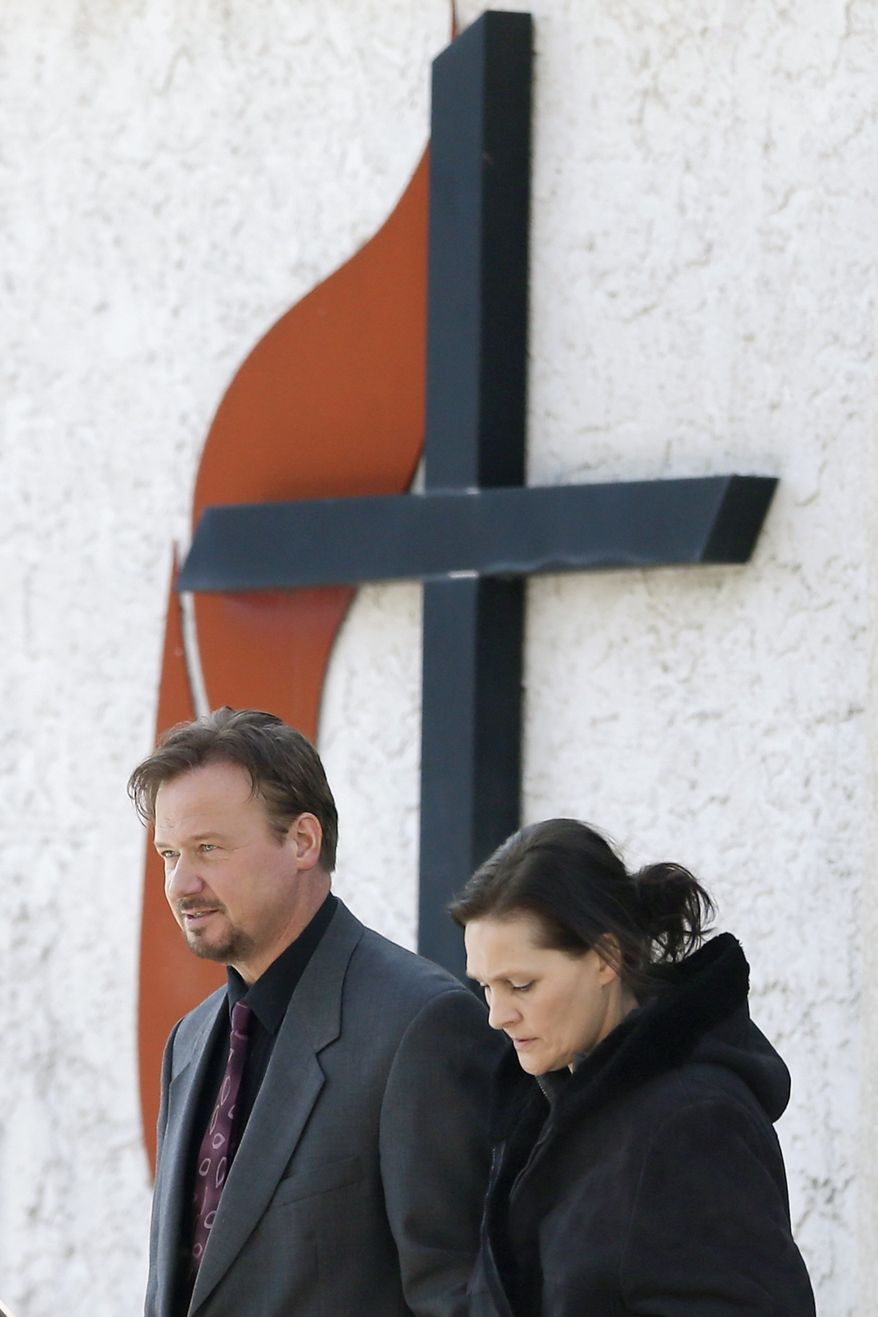 Accompanied by his wife Brigitte, right, the Rev. Frank Schaefer, of Lebanon, Pa., departs after a meeting with officials at the Eastern Pennsylvania Conference of the United Methodist Church, Thursday, Dec. 19, 2013, in Norristown, Pa. Church officials have defrocked Schaefer, who officiated his son's gay wedding in Massachusetts. (AP Photo/Matt Rourke)