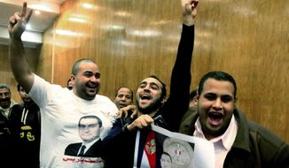 Egyptian supporters of former leader Hosni Mubarak celebrate after a court acquitted  Mubarak's two sons and his last prime minister of corruption charges, judiciary officials said at a court, in Cairo, Egypt, Thursday, Dec. 19, 2013. (AP Photo/Ahmed Abd El Latif, El Shorouk)