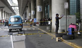 Police investigators examine the bloodstained pavement at the Terminal 3 of the Ninoy Aquino International Airport following an ambush of a southern Philippine town mayor Friday, Dec. 20, 2013, at suburban Pasay city south of Manila, Philippines.  Labangan Mayor Ukol Talumpa was fatally shot Friday in an attack at Manila's main airport that also killed his wife and two other people, officials said.(AP Photo/Bullit Marquez)