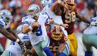 Cowboys quarterback Tony Romo scrambles to avoid the pursuit of Redskins linebacker Rob Jackson to keep a drive alive during the fourth quarter Sunday. (preston keres/special to the washington times)