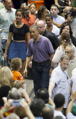 President Obama (center), and his daughter, Malia (left), arrive at the Stan Sheriff Center before the start of the Oregon State-Akron NCAA college basketball game at the Diamond Head Classic in Honolulu on Dec. 22, 2013. The President's brother-in-law Craig Robinson is the head coach of Oregon State. (Associated Press)
