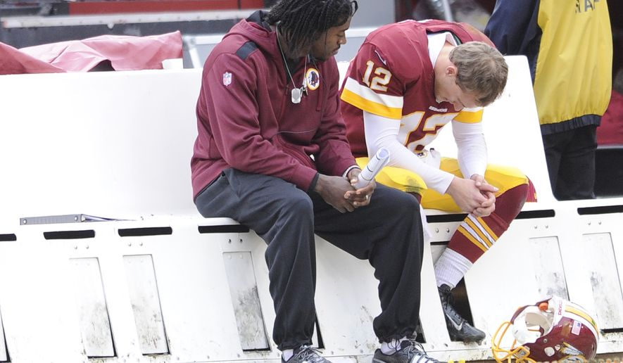 Washington Redskins quarterback Robert Griffin III talks with Redskins quarterback Kirk Cousins (12) after Cousins threw an interception as the Washington Redskins play the Dallas Cowboys at FedExField, Landover, Md., December 22, 2013. (Dan DeCook/Special to The Washington Times)