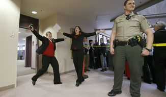 Becky Dustin, left, and Jennifer Rasmussen, right, exit the Salt Lake County clerk's office with their marriage license Monday, Dec 23, 2013.  On Friday, a Federal Judge Robert Shelby that Utah's Amendment 3 is unconstitutional. Utah is one of 33 states that enacted constitutional ban on same-sex marriage. In 2004, 66 percent of Utahns approved Amendment 3 and its traditional definition of marriage. (AP Photo/Deseret News, Ravell Call)