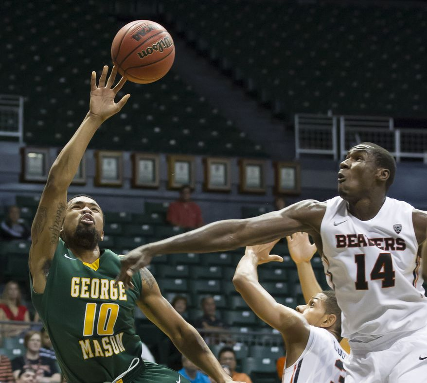 Oregon State forward Daniel Gomis (14) attempts to block a shot byGeorge Mason guard Sherrod Wright (10) during the first half of an NCAA college basketball game at the Diamond Head Classic on Monday, Dec. 23, 2013, in Honolulu. (AP Photo/Eugene Tanner)