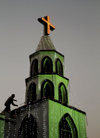 An Indian man decorates a church with lights ahead of Christmas in the eastern Indian city of Bhubaneswar, India, Monday, Dec. 23, 2013. Although Christians comprise only two percent of the population, Christmas is a national holiday and is observed across the country as an occasion to celebrate. (AP Photo/Biswaranjan Rout)