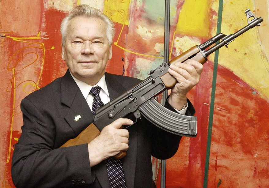 """FILE - In this July 26, 2002 file photo, Russian weapon designer Mikhail Kalashnikov presents his legendary assault rifle to the media while opening the exhibition """"Kalashnikov - legend and curse of a weapon"""" at a weapons museum in Suhl, Germany. Mikhail Kalashnikov, whose work as a weapons designer for the Soviet Union is immortalized in the name of the world's most popular firearm, has died at the age of 94, Monday Dec. 23, 2013. (AP Photo/Jens Meyer, File)"""