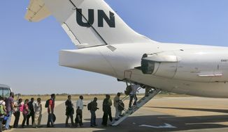 In this photo taken Sunday, Dec. 22, 2013 and released by the United Nations Mission in South Sudan (UNMISS) on Monday, Dec. 23, 2013, UNMISS relocates non-critical staff from Juba, South Sudan, to Entebbe, Uganda. Civilian helicopters evacuated U.S. citizens from the violent South Sudan city of Bor, capital of Jonglei state, seeing bouts of heavy machine gun fire, but 3,000 citizens from countries like Canada, Britain and Kenya remain trapped there, a top U.N. official said Monday. (AP Photo/UNMISS, Irene Scott)