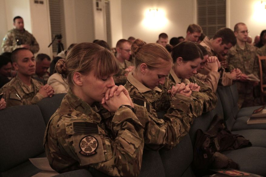 U.S. soldiers and service members with the NATO-led International Security Assistance Force (ISAF) attend a religious ceremony on Christmas Eve at Bagram military base in Kabul, Afghanistan, Tuesday Dec. 24, 2013. (AP Photo/Rahmat Gul)