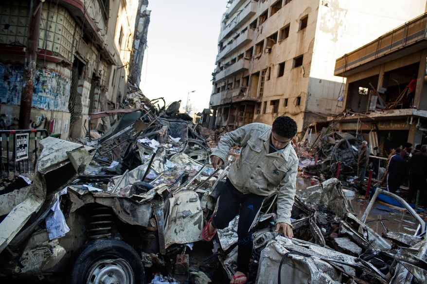 """An Egyptian man makes his way through rubble at the scene of an explosion at a police headquarters building that killed at least a dozen people, wounded more than 100, and left scores buried under the rubble, in the Nile Delta city of Mansoura, 110 kilometers (70 miles) north of Cairo, Egypt, Tuesday, Dec. 24, 2013. The country's interim government accused the Muslim Brotherhood of orchestrating the attack, branding it a """"terrorist organization."""" No one immediately claimed responsibility for the bombing, which came a day after an al-Qaida-inspired group called on police and army personnel to desert or face death at the hands of its fighters. (AP Photo/Ahmed Ashraf)"""