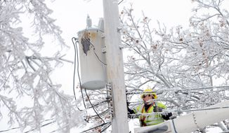 Dave Dora, a lineman from Grand Haven Board of Light and Power, works on connecting fallen wires on Macon Avenue in Lansing, Mich., Monday, Dec. 23, 2013. From Michigan to Maine, hundreds of thousands remain without power days after a massive ice storm _ which one utility called the largest Christmas-week storm in its history _ blacked out homes and businesses in the Great Lakes and Northeast. (AP Photo/Lansing State Journal, Greg DeRuiter)