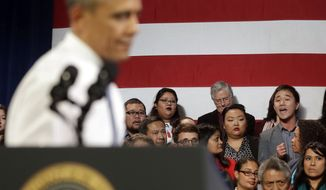 ** FILE ** In this Nov. 25, 2013, file photo, President Barack Obama, left, stops his speech and turns around in response to an unidentified man, right, who heckled him about anti-deportation policies, at the Betty Ann Ong Chinese Recreation Center in San Francisco. (AP Photo/Pablo Martinez Monsivais, File)