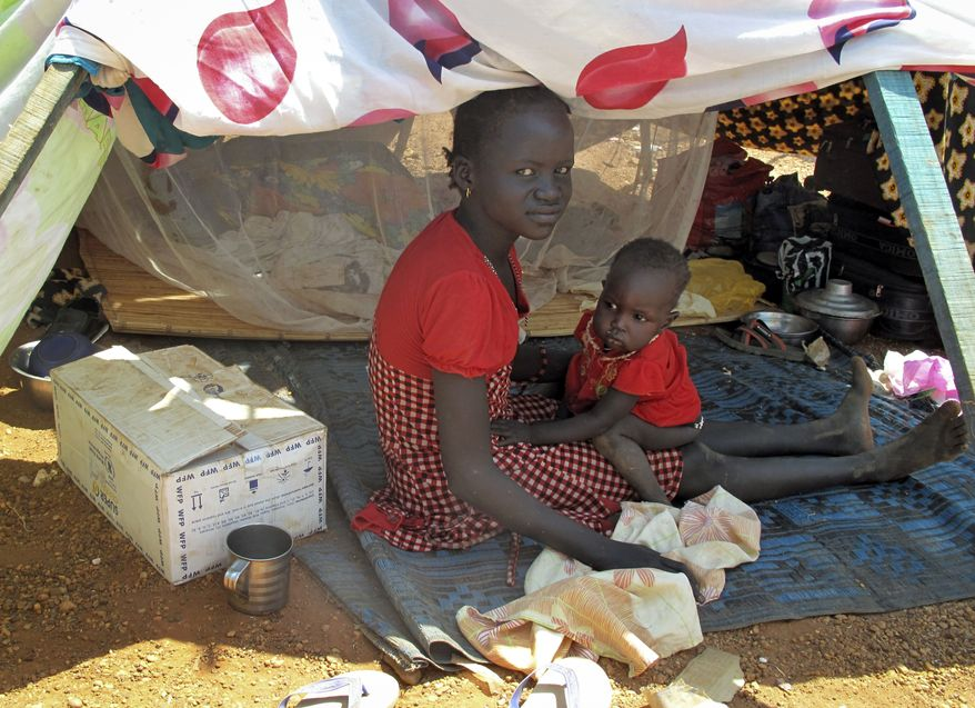In this photo taken Monday, Dec. 23, 2013 and released by the World Food Programme (WFP), a woman and child sit in the shade next to a box of food assistance they have received in the UN compound where they have sought shelter in Juba, South Sudan. South Sudan's military spokesman says there is increasing tension at a United Nations camp in the rebel-held city of Bor because armed elements have entered the congested area where the U.N. says about 17,000 civilians are seeking protection. (AP Photo/WFP, George Fominyen)
