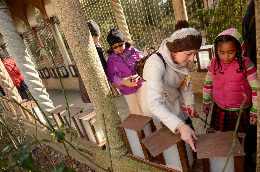 Kelly Hutchison of Hyattsville, Md., second from right, and her two daughters Lauren, 10, center, and Lindsey, 7, right, help light nearly 1,000 luminarias set up along the exterior of the historic Franciscan Monastery of the Holy Land, Washington, D.C., Tuesday, December 24, 2013. The luminaries, which will remain lit through New Year's Eve, are each dedicated to an individual for whom prayers will be offered throughout Christmas week.(Andrew Harnik/The Washington Times)