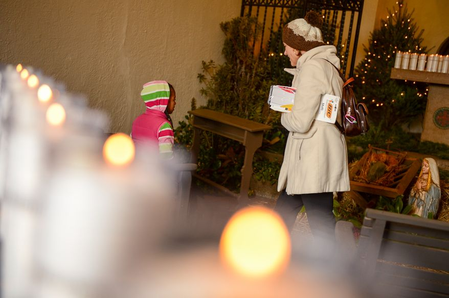 Lindsey, 7, and her mother Kelly Hutchison of Hyattsville, Md., stop to look at a manger scene after helping to light nearly 1,000 luminarias set up along the exterior of the historic Franciscan Monastery of the Holy Land, Washington, D.C., Tuesday, December 24, 2013. The luminaries, which will remain lit through New Year's Eve, are each dedicated to an individual for whom prayers will be offered throughout Christmas week.