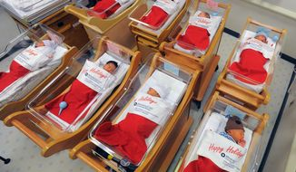 Newborns sleep in oversized red stockings in the nursery at Long Beach Memorial in Long Beach, Calif., on Monday, Dec. 23, 2013. For more than 50 years, babies born between Dec. 21-25 at Long Beach Memorial are placed in big red stockings to be presented to the new parents.(AP Photo/Daily Breeze, Scott Varley)