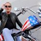 "Peter Fonda, who played Captain America in ""Easy Rider,"" poses atop a Harley-Davidson based on the motorcycle he rode in the counterculture film released in 1969. The young Mr. Fonda and his sister, Jane (below), who also joined the family business, board a flight to Europe with their father in summer 1957. (associated press)"