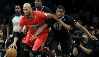 Brooklyn Nets' Joe Johnson, right, and Andray Blatche, center, pursue Chicago Bulls' Taj Gibson during the first half of the NBA basketball game at the Barclays Center Wednesday, Dec. 25, 2013, in New York. (AP Photo/Seth Wenig)