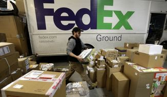 ** FILE ** In this Dec. 16, 2013, file photo, package handler Chris Addison arranges packages before loading a delivery truck at a FedEx sorting facility in Kansas City, Mo. Santa's sleigh didn't make it in time for Christmas for some this year due to shipping problems at UPS and FedEx. The delays were blamed on poor weather earlier this week in parts of the country as well as overloaded systems.  (AP Photo/Charlie Riedel)