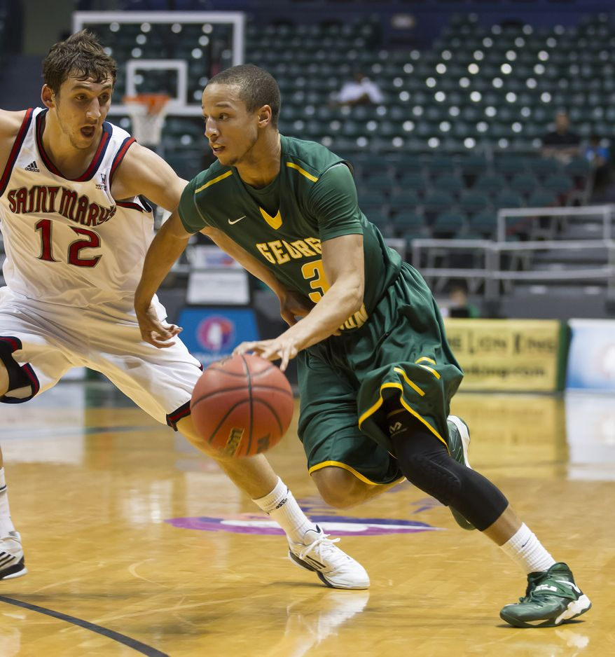 George Mason guard Patrick Holloway (3) drives the baseline as Saint Mary's (Calif.) guard Jordan Giusti (12) guards Holloway during the first half of an NCAA college basketball game at the Diamond Head Classic on Wednesday, Dec. 25, 2013, in Honolulu. George Mason won 65-63. (AP Photo/Eugene Tanner)
