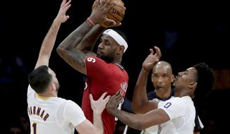 Miami Heat forward LeBron James, middle, is double-teamed by Los Angeles Lakers' Jordan Farmar, left, and Nick Young during the first half of an NBA basketball game in Los Angeles, Wednesday, Dec. 25, 2013. (AP Photo/Chris Carlson)