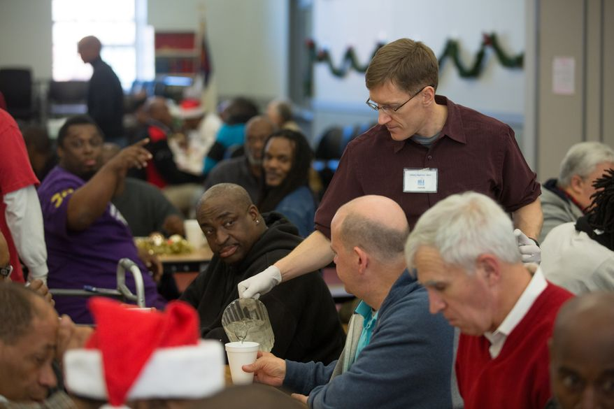 Jason Clark, a volunteer, pours water for homeless guests at the Central Union Mission during the annual Christmas Day lunch, in Washington, DC., Wednesday, December 25, 2013.  (Andrew S Geraci/The Washington Times)