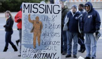 FILE - In this Nov. 23, 2013 file photo, college football fans pause at the sight outside Beaver Stadium where there once stood a bronze statue of long-time Penn State football coach Joe Paterno before an NCAA college football game between Penn State and Nebraska in State College, Pa. The Nittany Lions have had two years of modified success under coach Bill O'Brien, and as the program, school and town continue to push past the Jerry Sandusky scandal, the focus is clearly on moving forward in this new era as a community, as a team, and as Nittany Lions.  (AP Photo/Gene J. Puskar, File)