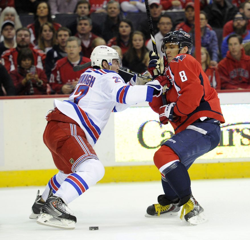 Washington Capitals right wing Alex Ovechkin (8), of Russia, battles for the puck against New York Rangers defenseman Ryan McDonagh, left, during the first period an NHL hockey game, Friday, Dec. 27, 2013, in Washington. (AP Photo/Nick Wass)