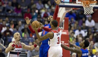 Washington Wizards' Bradley Beal (3) passes the ball to teammate Marcin Gortat (4), of Poland, while Detroit Pistons center Andre Drummond (0) defends during the first half of an NBA basketball game in Washington, Saturday, Dec. 28, 2013. The Wizards won 106-82. (AP Photo/Manuel Balce Ceneta)