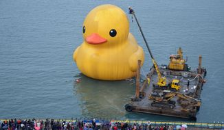 ** FILE ** Cleaners scrub a giant yellow duck at Keelung port in New Taipei City, Taiwan, Saturday, Dec. 28, 2013. The famous 18-meter (59-foot) rubber duck, created by Dutch artist Florentijn Hofman, was cleaned up during its Taiwan tour. (AP Photo)
