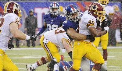 New York Giants' Spencer Paysinger (54) tackles Washington Redskins' Alfred Morris (46) during the first half of an NFL football game Sunday, Dec. 29, 2013, in East Rutherford, N.J.  (AP Photo/Bill Kostroun)