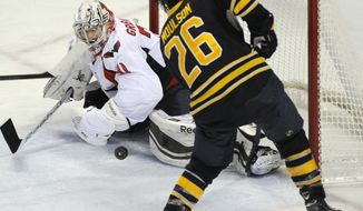 Buffalo Sabres left winger Matt Moulson (26) shoots on Washington Capitals goaltender Philipp Grubauer, of Germany, during the third period of an NHL hockey game in Buffalo, N.Y., Sunday, Dec. 29, 2013. Buffalo won 2-1. (AP Photo/Gary Wiepert)