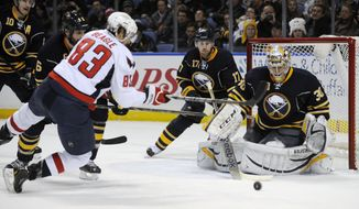 Washington Capitals' Jay Beagle (83) shoots the puck as he falls while Sabres Christian Ehrhoff (10) Mike Weber (6) Linus Omark (17) and Ryan Miller (30) defend during the second period of an NHL hockey game in Buffalo, N.Y., Sunday, Dec. 29, 2013. (AP Photo/Gary Wiepert)