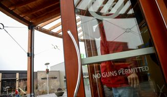 "Signs reading ""no guns permitted"" are displayed on the front doors to Toby Keith's I Love this Bar & Grill, Woodbridge, Va., Sunday, December 29, 2013. (Andrew Harnik/The Washington Times)"