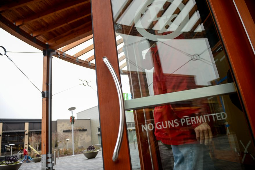 """Signs reading """"no guns permitted"""" are displayed on the front doors to Toby Keith's I Love this Bar & Grill, Woodbridge, Va., Sunday, December 29, 2013. (Andrew Harnik/The Washington Times)"""