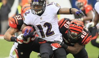Baltimore Ravens wide receiver Jacoby Jones (12) is tackled by Cincinnati Bengals linebacker Michael Boley (53) and strong safety Shawn Williams (40) in the first half of an NFL football game, Sunday, Dec. 29, 2013, in Cincinnati. (AP Photo/Tom Uhlman)