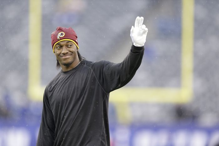 Washington Redskins quarterback Robert Griffin III walks the field before an NFL football game against the New York Giants Sunday, Dec. 29, 2013, in East Rutherford, N.J.  (AP Photo/Julio Cortez)