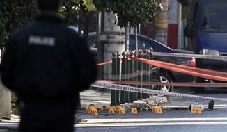 Yellow evidence markers are placed where bullet casings were found after an attack outside the residence of German ambassador to Athens, Wolfgang Dold, in the northern suburb of Halandri, Greece on Monday, Dec. 30, 2013. (AP Photo/Thanassis Stavrakis)
