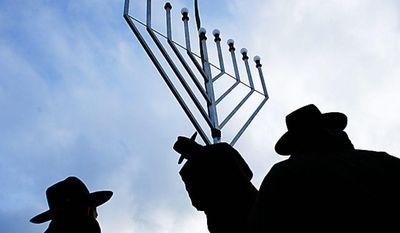 Rabbi Yehuda Teichtal, center, installs with other Rabbis a giant Hanukkah Menorah at the launch of the eight-day Jewish Festival of Lights, named Hanukkah, at the Pariser Platz near the Brandenburg Gate in central Berlin on Wednesday, Dec. 1, 2010. (AP Photo/Markus Schreiber)