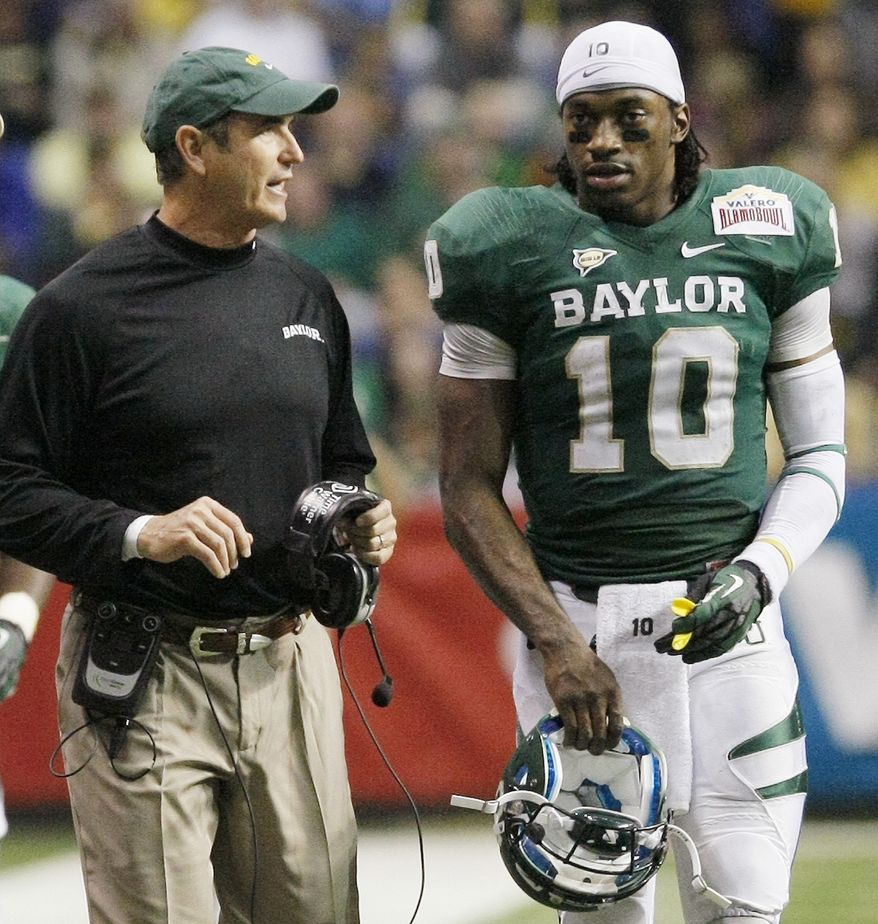 Baylor head coach Art Briles, left, and quarterback Robert Griffin III talk during the second half of the Alamo Bowl college football game against Washington, Thursday, Dec. 29, 2011, at the Alamodome in San Antonio. Baylor pulled out a thrilling Alamo Bowl victory in the highest-scoring bowl game in history, beating Washington 67-56 in a record-smashing shootout Thursday night. (AP Photo/Darren Abate)