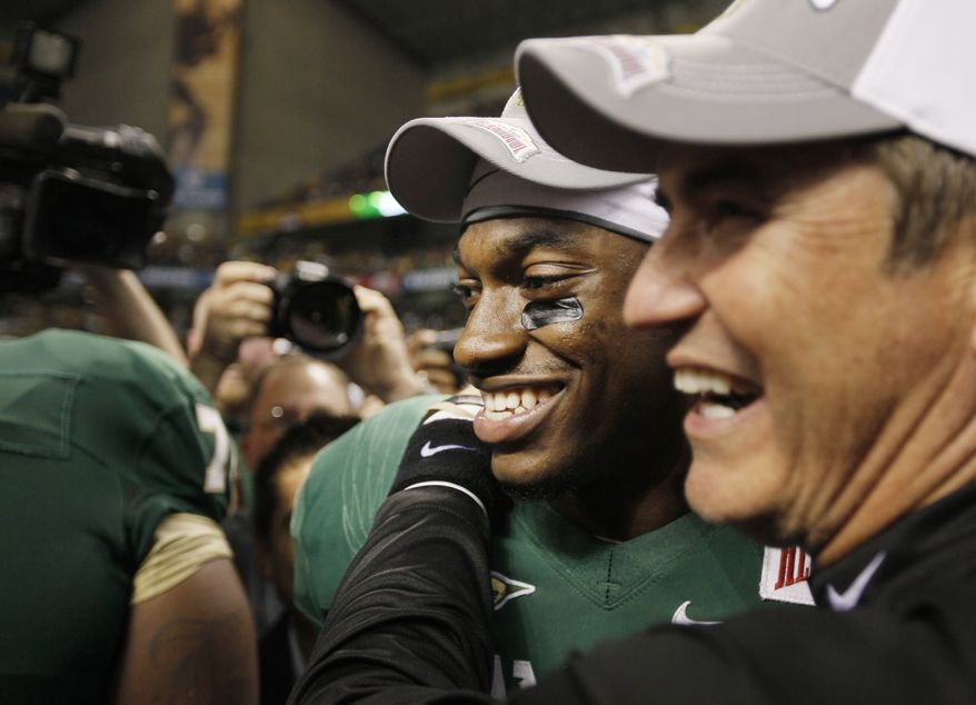 Baylor quarterback Robert Griffin III, left, celebrates with Baylor head coach Art Briles after the Alamo Bowl college football game, Thursday, Dec. 29, 2011, at the Alamodome in San Antonio. Baylor pulled out a thrilling Alamo Bowl victory in the highest-scoring bowl game in history, beating Washington 67-56 in a record-smashing shootout Thursday night. (AP Photo/Darren Abate)
